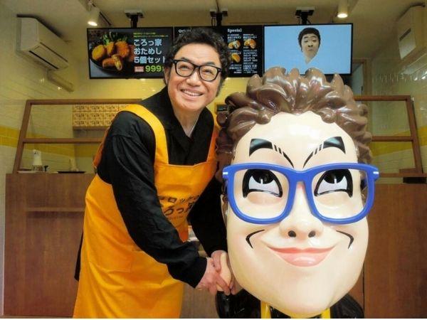 「コロッケのころっ家」の店頭にて、コロッケと大きな顔のフィギュア